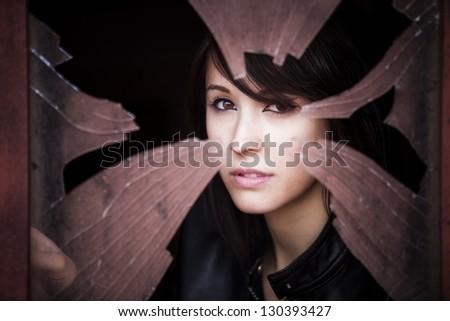 Woman looking through dirty broken glass - stock photo