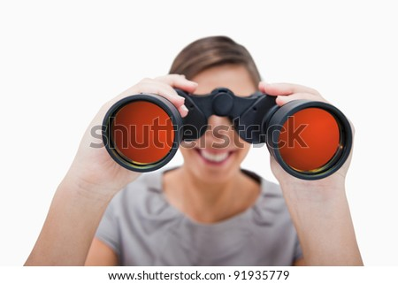Woman looking through spyglasses against a white background - stock photo