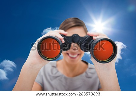 Woman looking through spyglasses against bright blue sky with clouds - stock photo
