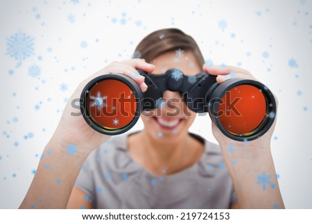 Woman looking through spyglasses against snow falling - stock photo