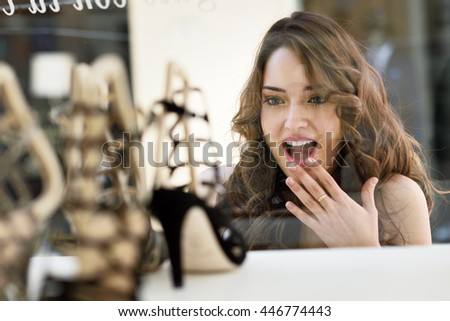 Woman looking to showcase or shop window. Shopping girl chooses shoes in store - stock photo