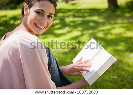 Woman looking towards her side and smiling while reading a book as she sits down in the grass - stock photo