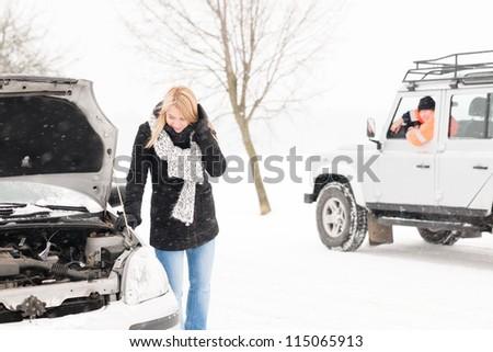 Woman looking under broken car hood snow trouble man assistance - stock photo
