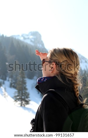Woman looking up on a mountain in winter - stock photo