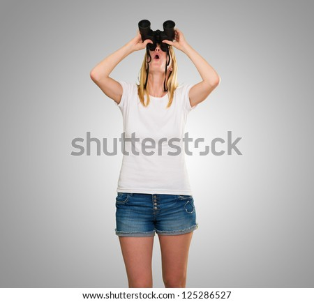 woman looking up using binoculars against a grey background - stock photo