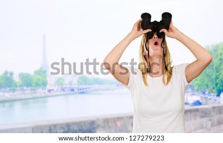 woman looking up using binoculars, outdoor - stock photo