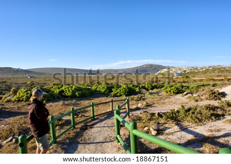 Woman looks at road running among hills. Shot in West Coast Nature Reserve, near Langebaan, Western Cape, South Africa. - stock photo