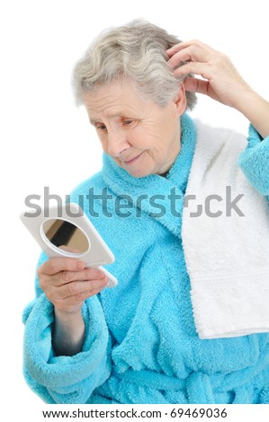 woman looks in a mirror on white background - stock photo