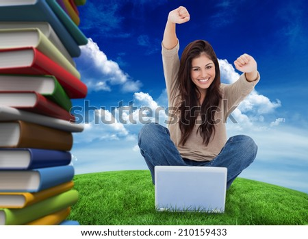 Woman looks straight ahead as she celebrates in front of her laptop against green field under blue sky - stock photo