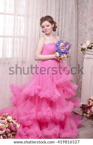 woman looks towards the violation of thinking on a pink background. Beautiful woman portrait in dress smiling fresh happy. Pretty mixed race Caucasian brunette fashion model - stock photo