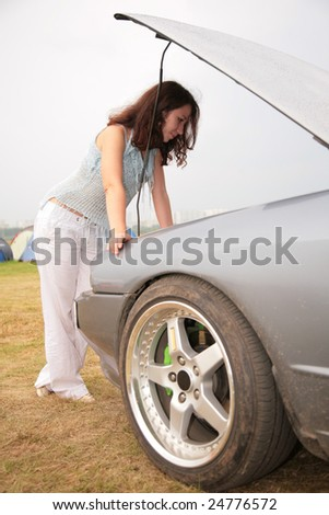 Woman looks under a car cowl - stock photo