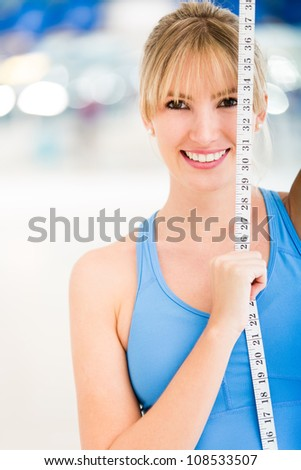Woman loosing inches at the gym holding a tape measure - stock photo
