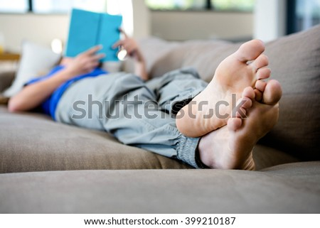 woman lying barefoot on the couch reading a book - stock photo