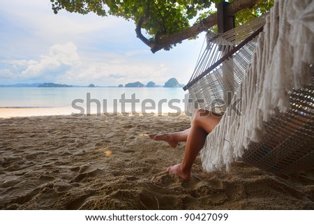 Woman lying in a hammock in tree's shadow on a beach - stock photo