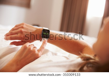 Woman Lying in Bed Whilst Checking Fitness App on Smart Watch - stock photo