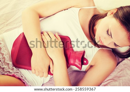 Woman lying in bed with hot water bag on belly. - stock photo
