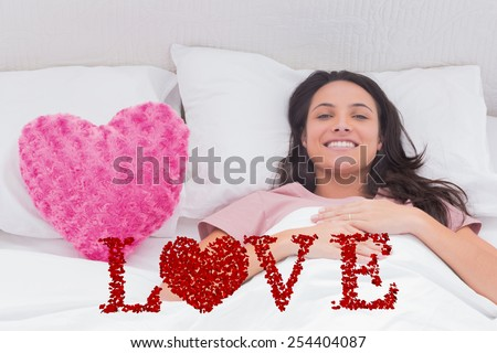 Woman lying in her bed next to a pink heart pillow against love spelled out in petals - stock photo