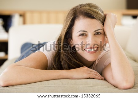 Woman lying in living room - stock photo