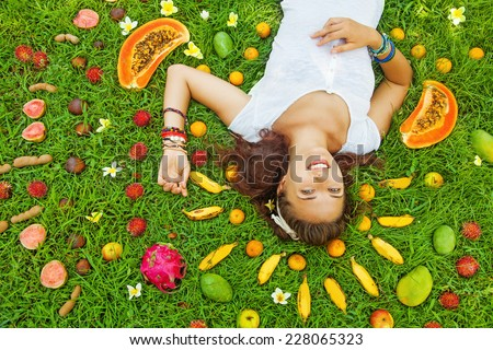 woman lying on a grass with the pattern of colorful fresh exotic fruits around - stock photo