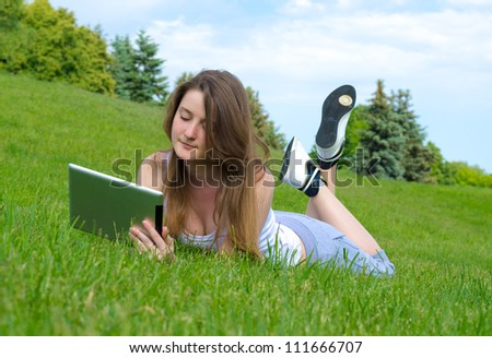 Woman lying on a grassy slope outdoors relaxing with a touchscreen tablet - stock photo