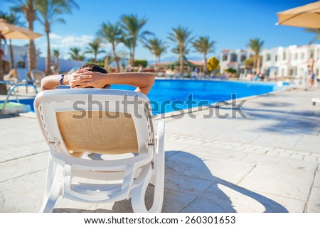 woman lying on a lounger by the pool at the hotel. - stock photo