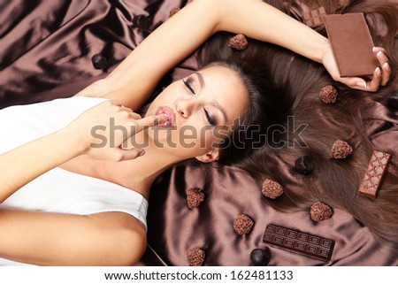 Woman lying on brown atlas covered by chocolate and candies - stock photo