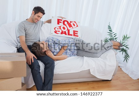 Woman lying on her husband in the couch in their new house while holding a sign with sold written on it - stock photo