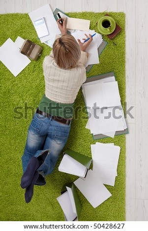 Woman lying on living room floor, doing financial calculation,holding credit card and pen, drinking coffee, in overhead view. - stock photo