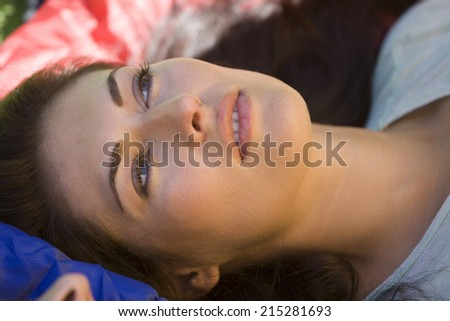 Woman lying on sleeping bag, daydreaming, side view, close-up - stock photo