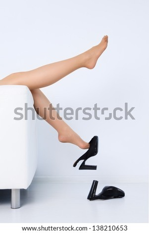 woman lying on sofa taking off high heel shoes - stock photo