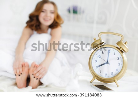 Woman lying on the bed and smiling. woman in morning holding feet. alarm clock in bedroom. Beautiful sexy brunette woman with beautiful long hair in white lingerie lying on back on white bed with feet - stock photo