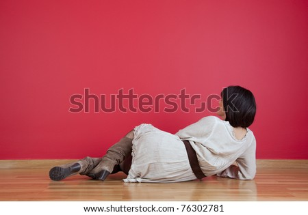 Woman lying on the floor looking to her fresh new red wall - stock photo
