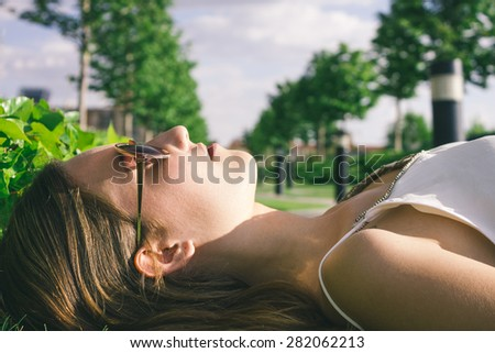 Woman lying on the grass - stock photo