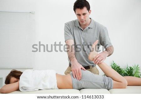Woman lying while being stretched by a physiotherapist in a room - stock photo