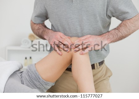 Woman lying with her legs folded while a man massaging her knee in a room - stock photo