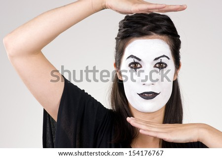 Woman made up in white face frames her features with her hands - stock photo