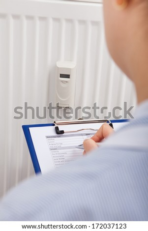 Woman Maintaining Records Of Digital Thermostat On Clipboard - stock photo