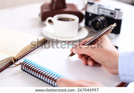 Woman makes a note in a notebook with a retro camera in the background - stock photo