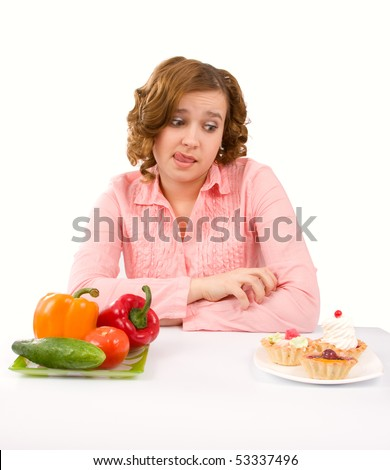 Woman makes choice between cakes and healthy vegetables on white background.  To eat or not to eat - stock photo