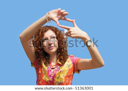 Woman making a frame of their hands. Girl has red wavy hair - stock photo
