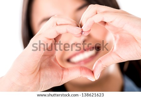 Woman making a heart shape with her hands - isolated over white - stock photo
