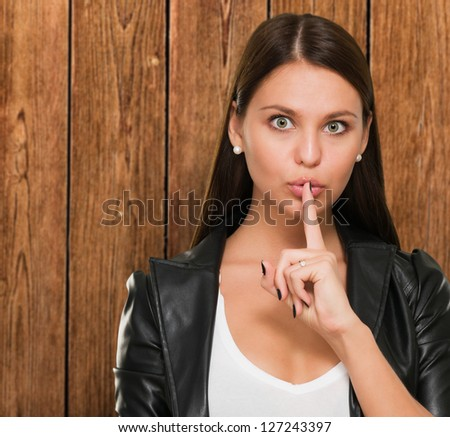 Woman Making A Keep It Quiet Gesture against a wooden background - stock photo