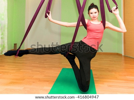 Woman making aerial yoga exercise in club, fly yoga - stock photo
