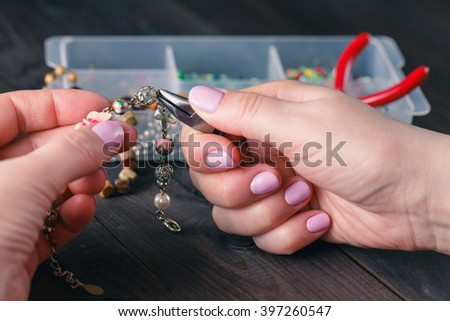 Woman making beads. Box with beads, spool of thread, plier and glass hearts to create hand made jewelry on old wooden background - stock photo