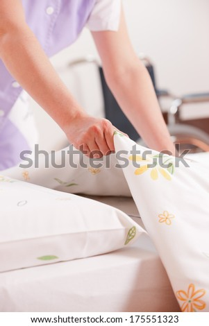 Woman making bed and changing bedding in guest room. - stock photo