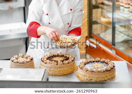 Woman making biscuit cake with nuts and chocolate at the bakery - stock photo