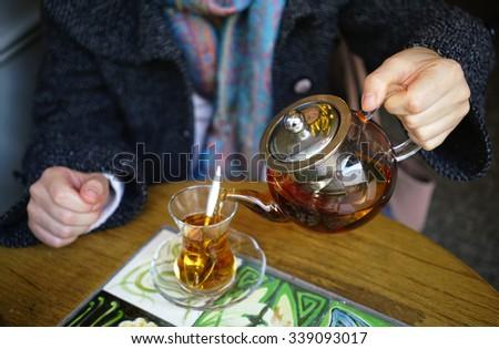 Woman Making black tea in cafe - stock photo