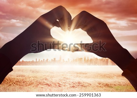 Woman making heart shape with hands against large city on the horizon - stock photo