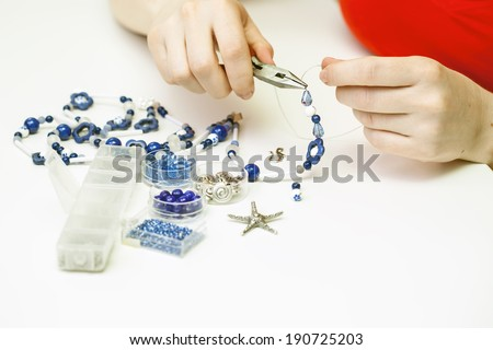 Woman making necklace from colorful gemstone beads - stock photo