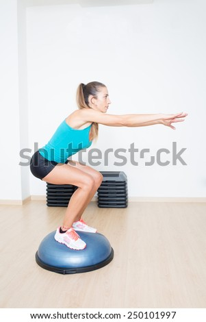 Woman making squats on balance trainer - stock photo